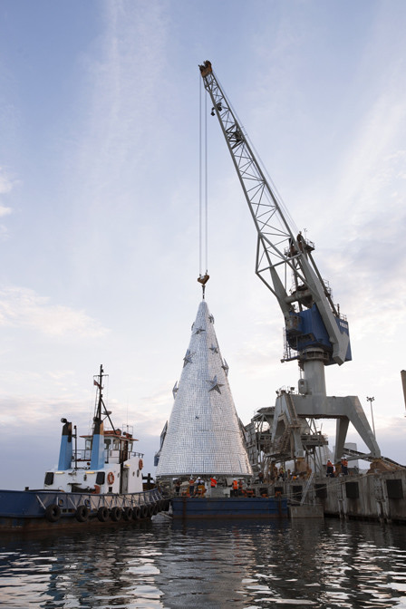 Christmas tree sculpture being installed by crane onto a floating platform in Geelong