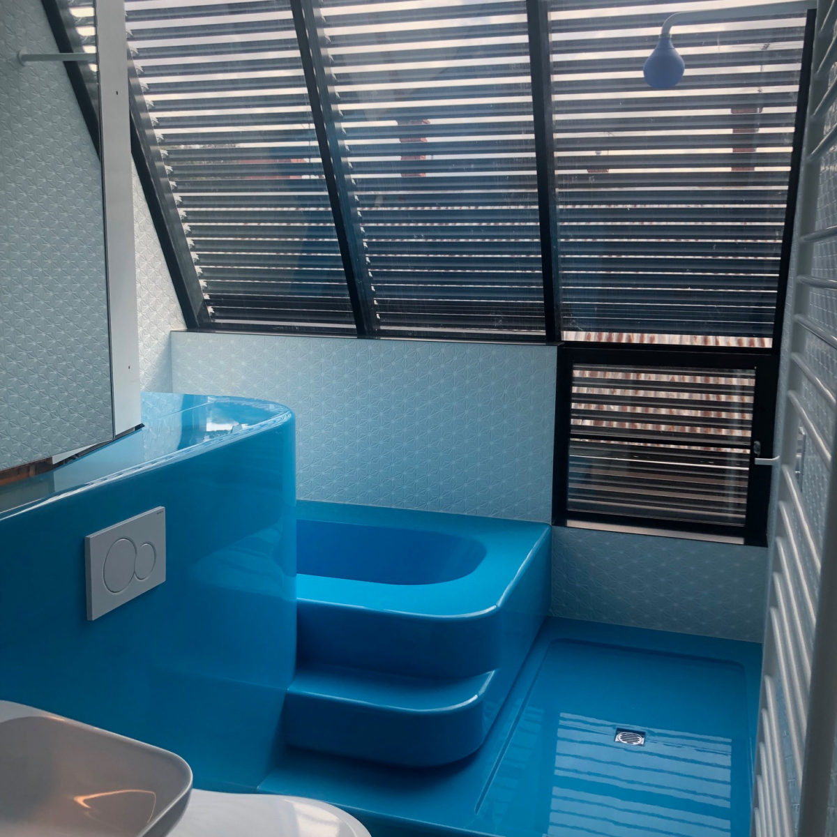 Bright blue floor and bathtub in bathroom with white tiles and louvered windows