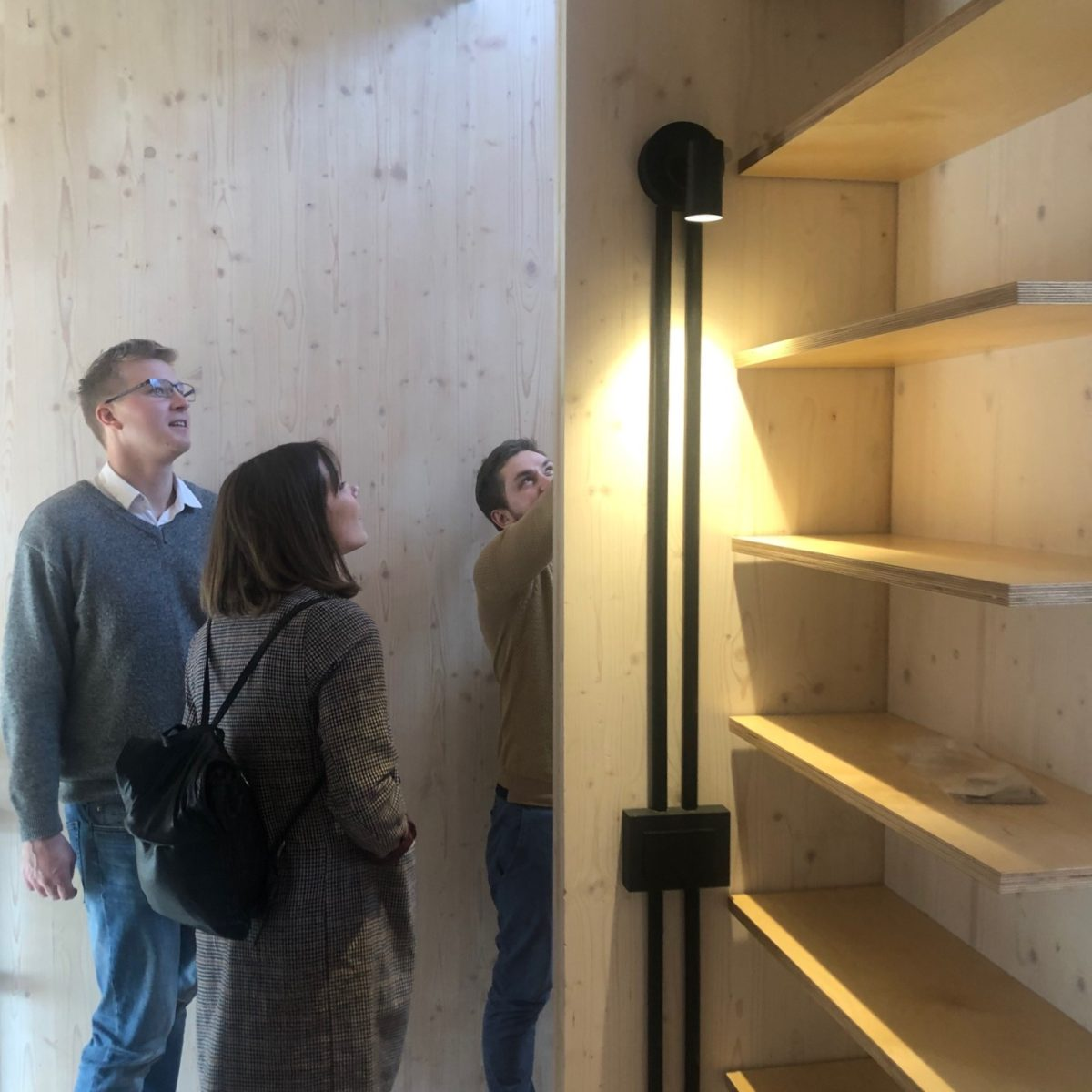 Vistek Engineers looking at detail in Union St CLT House hallway, with exposed timber walls and shelves. At Union St CLT House.