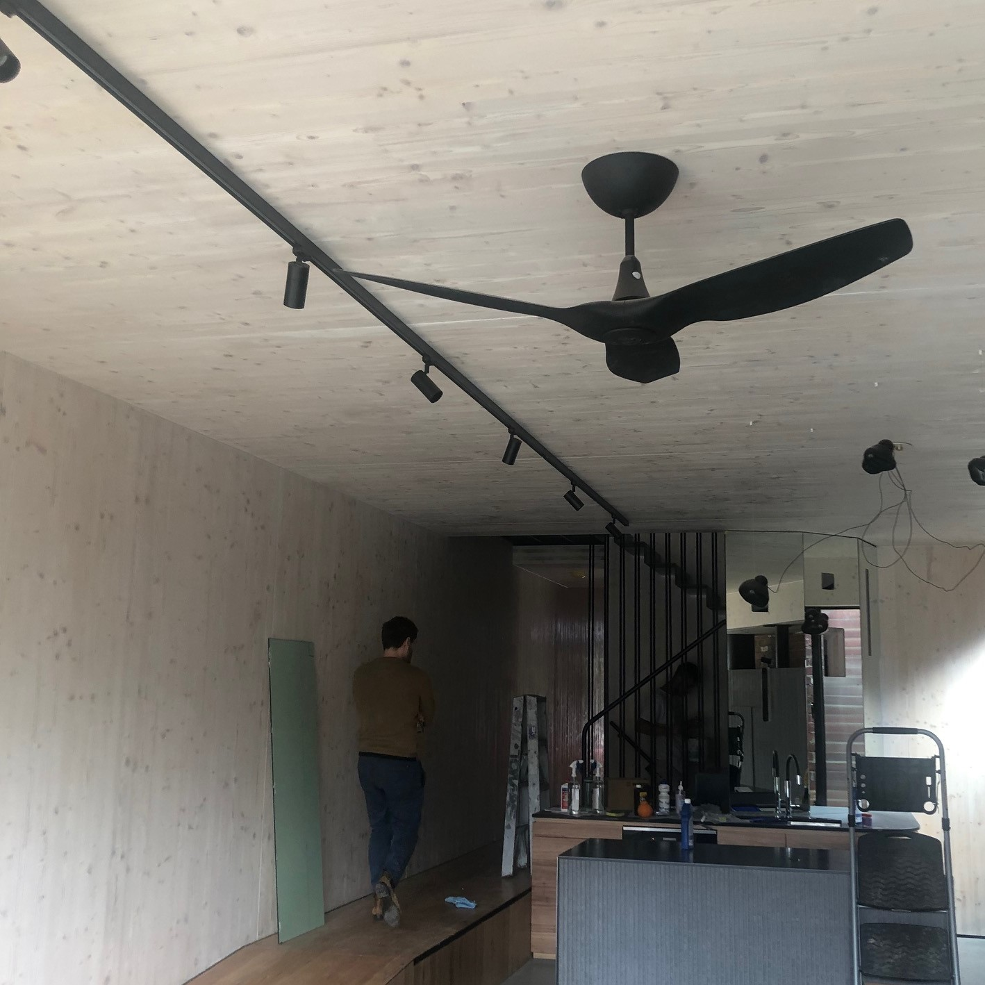 Interior of living room and kitchen with exposed timber and black ceiling fan and lighting strip