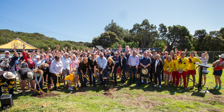 """Over 100 community members gather on the lawn, some with spades to """"turn the sod"""" for the start of construction"""