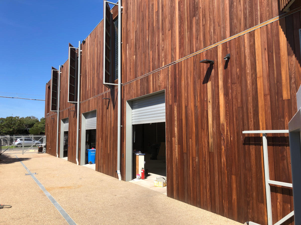 Rear access roller doors for lifesaving equiptment, in double storey timber clad wall
