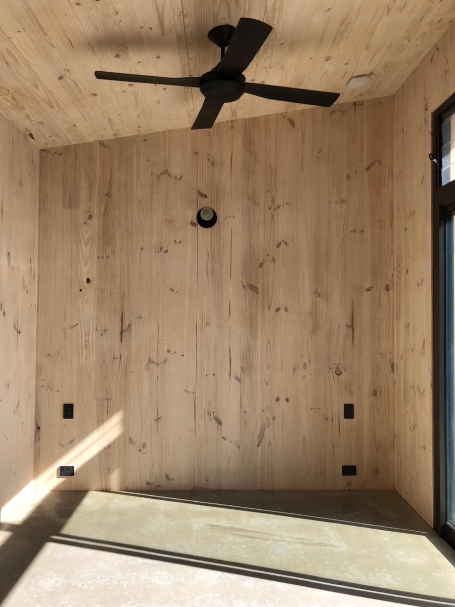 Bedroom of tiny house with exposed timber walls and ceiling fan