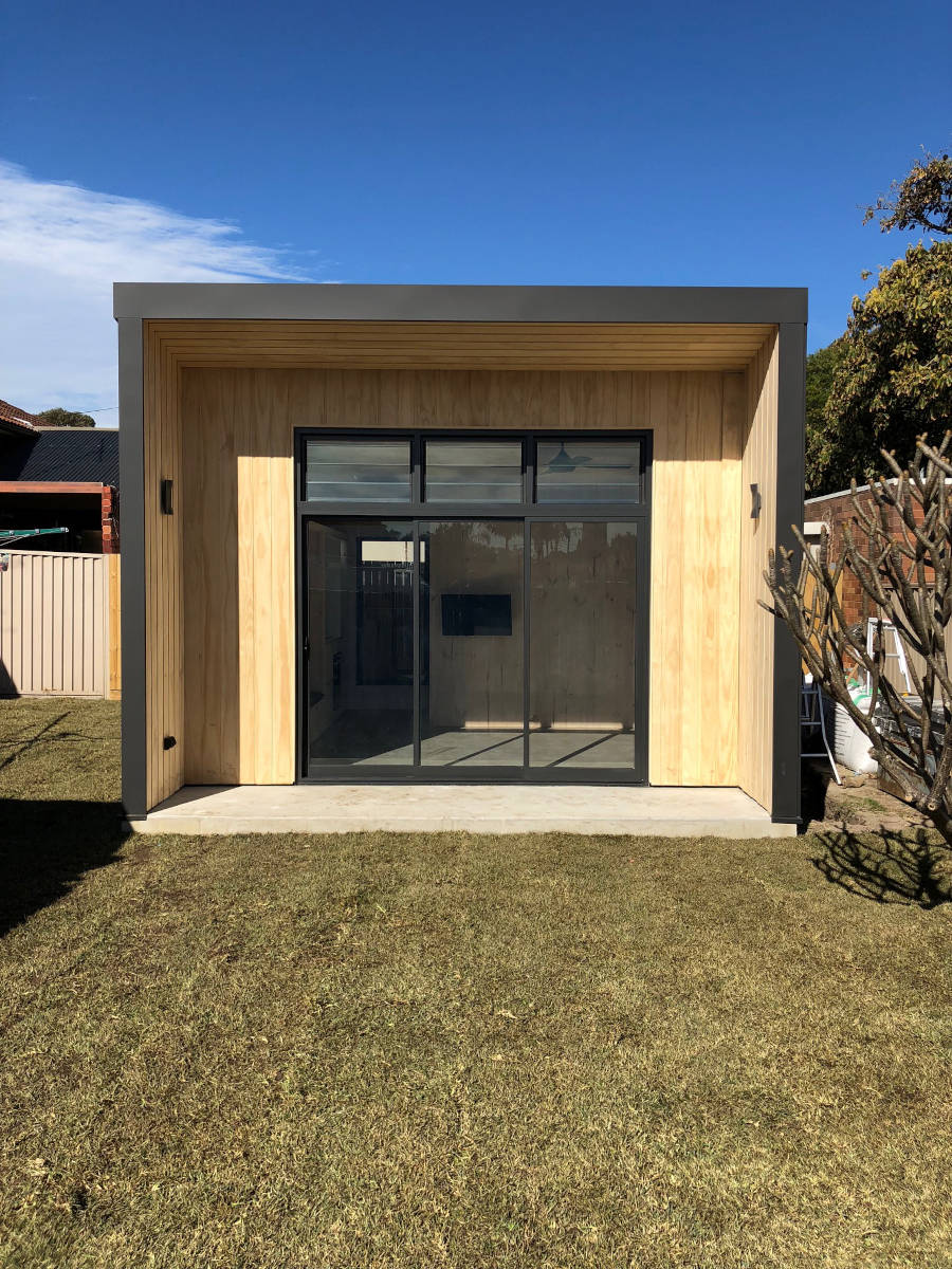 Front view of CLT tiny house, with exposed timber in the front alcove and glass sliding doors