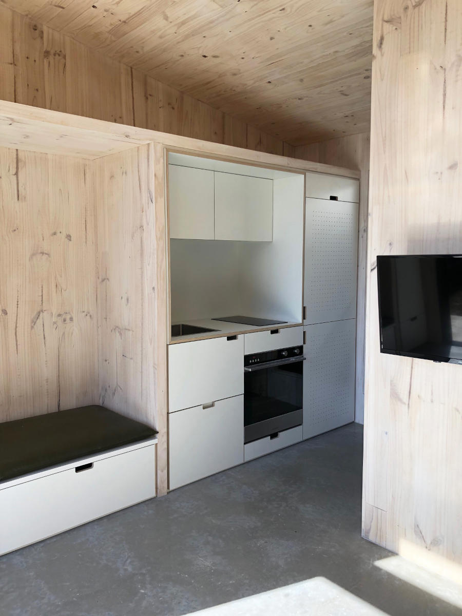 Kitchenette and living space of CLT tiny house, with exposed timber walls and white cabinets.