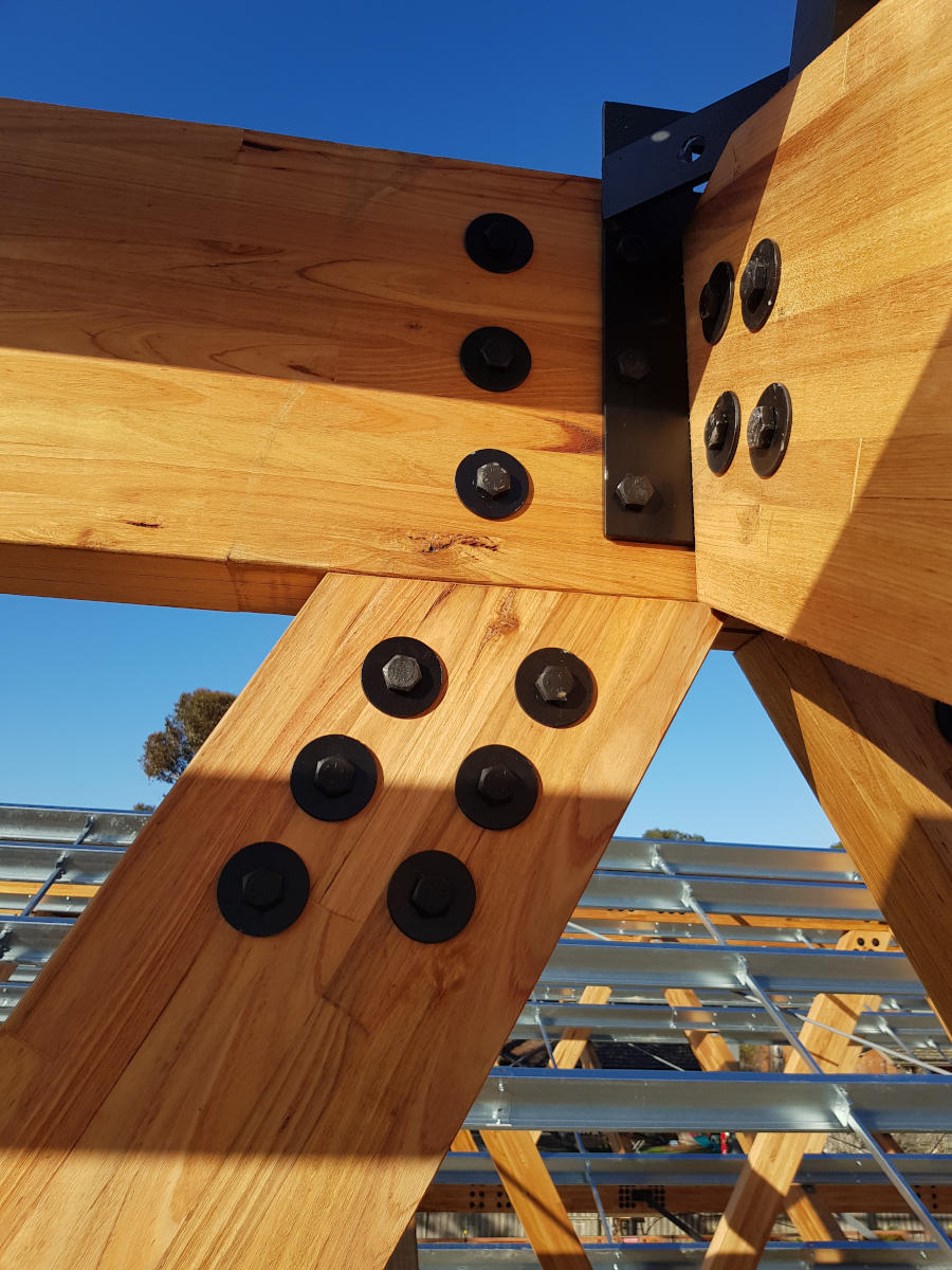 Connection detail with black bolts and plates at intersection of four timber trusses
