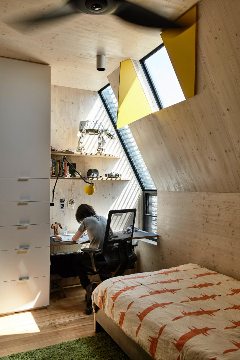 Nook with exposed timber walls and roof and angled windows, with child studying at a desk