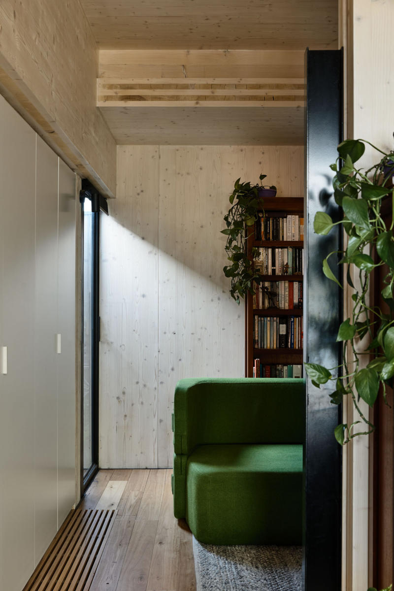 Light timber walls and floorboards with green couch bookshelves and plants