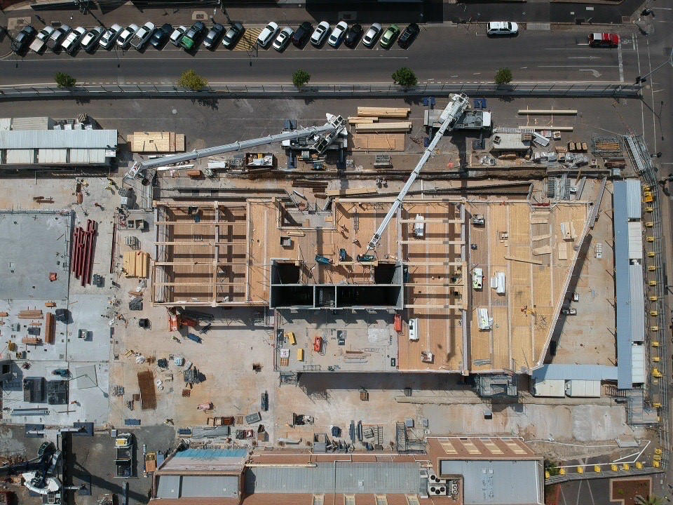Arial view of two cranes lifting Glulam beams into place during construction
