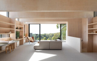 Exposed timber walls, shelving and desk in a livingroom with grey couch and wide window leading onto a balcony. Nominated for Timber Design Awards People's Choice 2020.