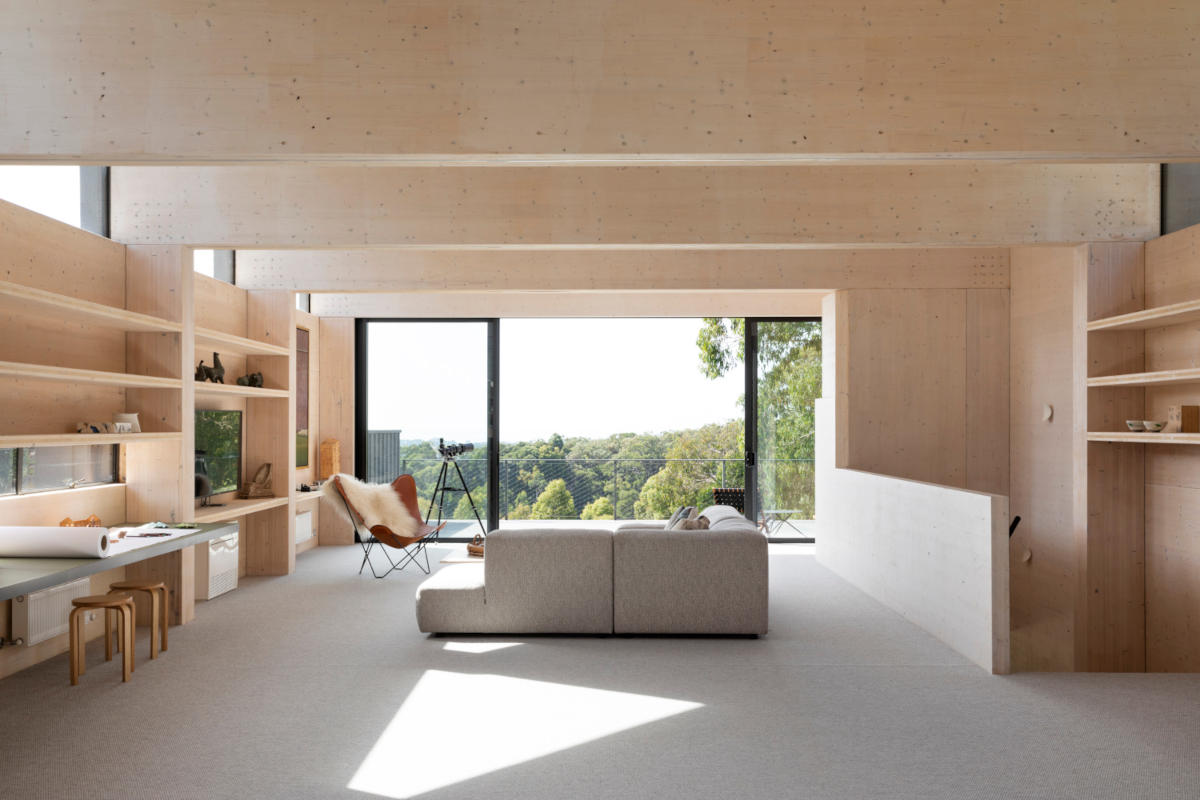 Exposed timber walls, shelving and desk in a livingroom with grey couch and wide window leading onto a balcony