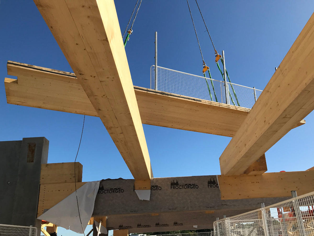 Detail of Cross Laminated Timber slab being positioned by crane onto Glue Laminated Timber beams