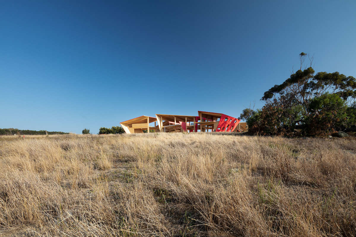 Ceres CLT and Mass Timber House. A geometric wooden house under construction in grassy field