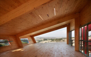 Ceres mass timber house including Glulam beams and CLT floor, wall and roof. Interior of large room with wooden floor, beams and sloping roof, and view of countryside through window at far end.