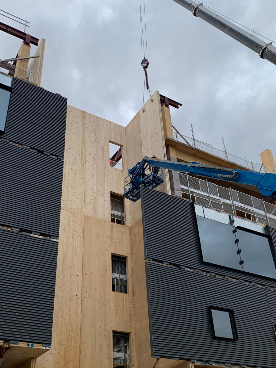Cladding being placed by crane and cherry picker