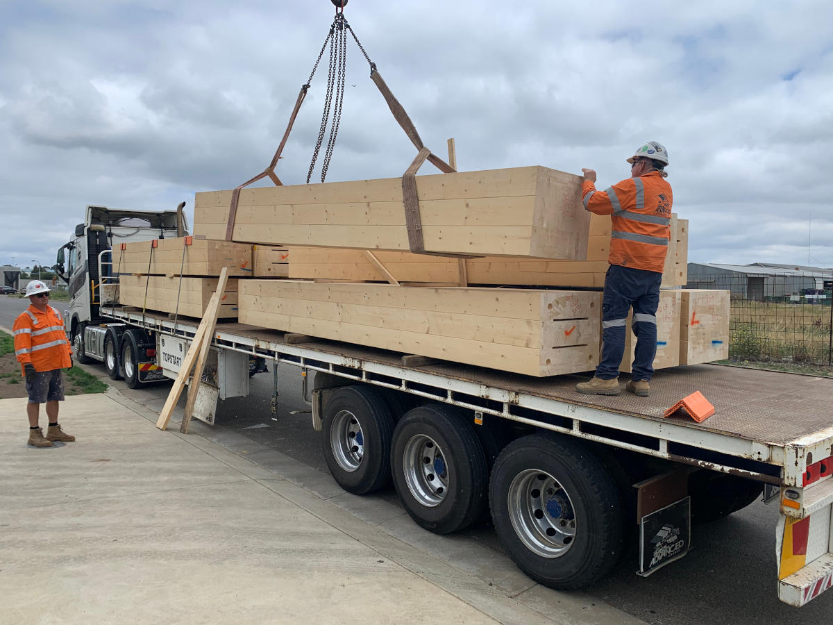 Glue Laminated Timber (GLT, Glulam) beams arriving by flat bed truck