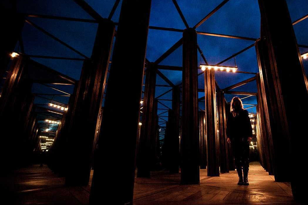 Person standing in a house of mirrors at night. Art installation engineered by Vistek Structural Engineers.