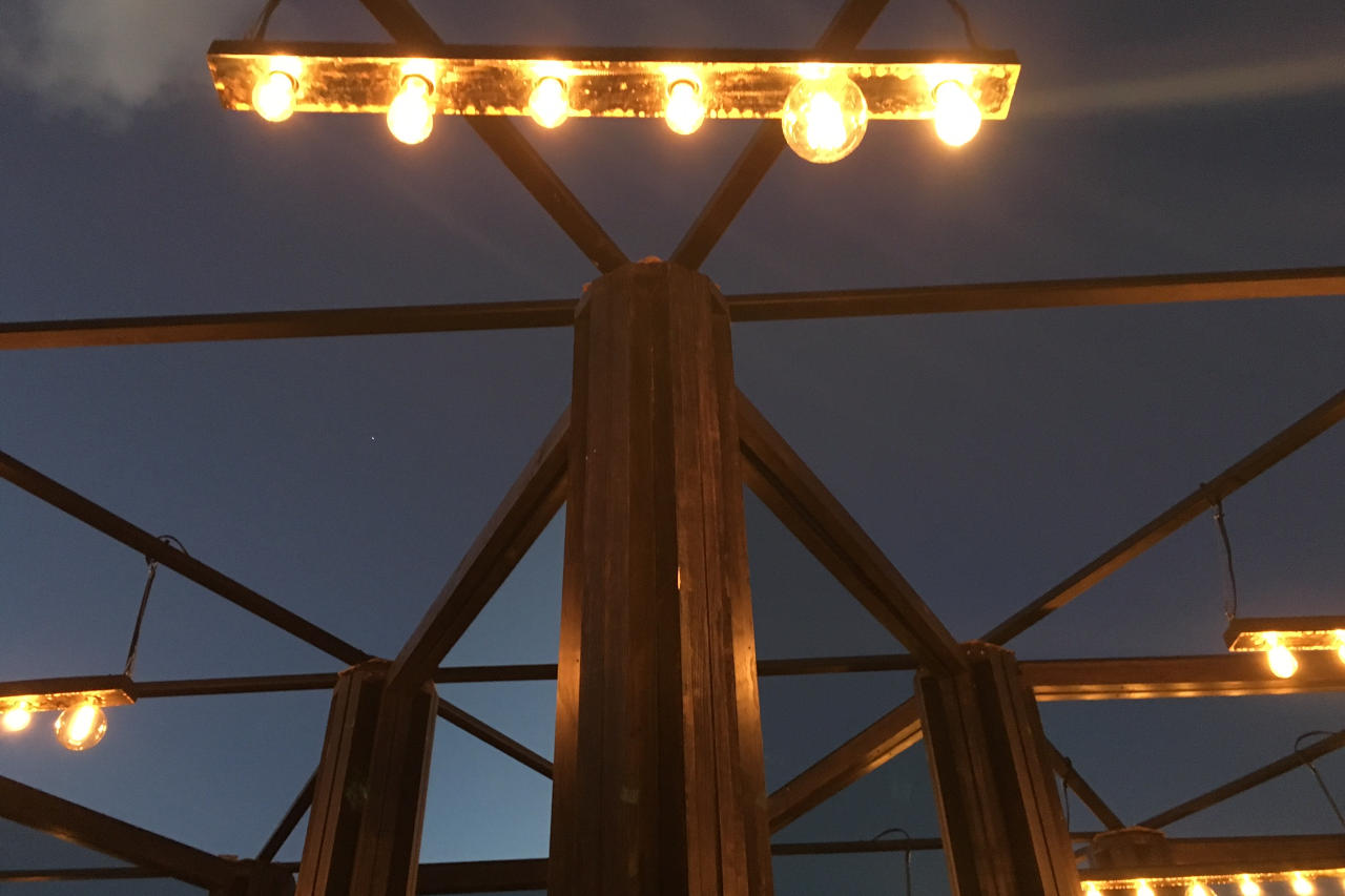 Detail of lights and geometric roof structure of CPS's House of Mirrors at night